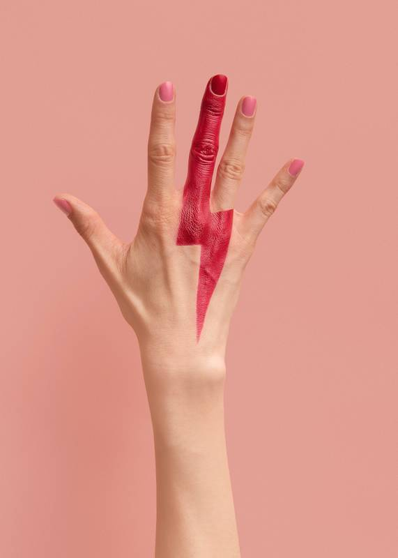 A hand with a lightning bolt painted on it with a red lipstick. Image by re:design studio.