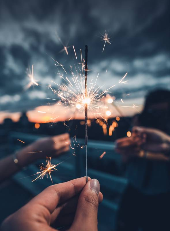 photo of person holding lighted sparkler