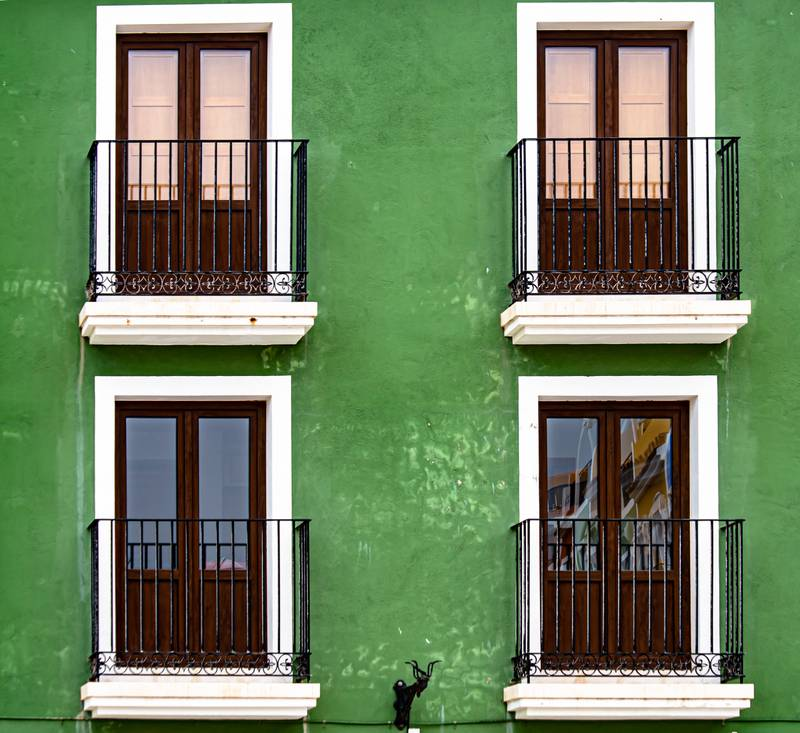 green concrete building with black metal window grill