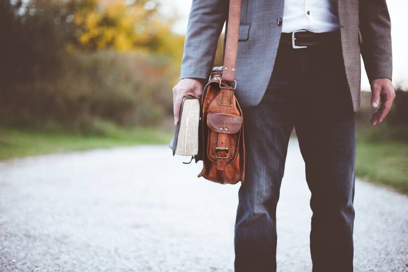 Man with leather bag and book