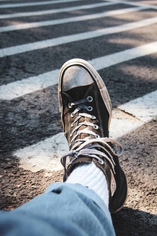 person in blue denim jeans and brown and white converse all star high top sneakers