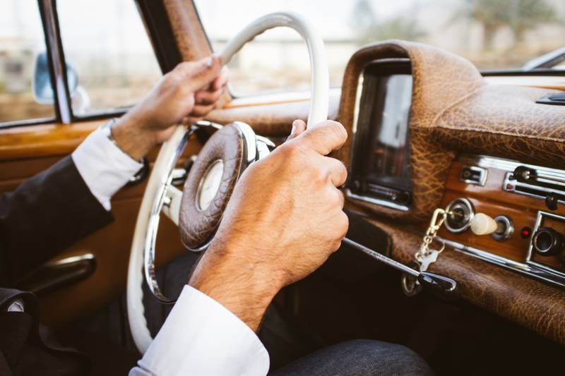 person holding vehicle steering wheel