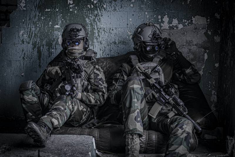 Airsoft players in protective glasses and helmet, with the airsoftgun