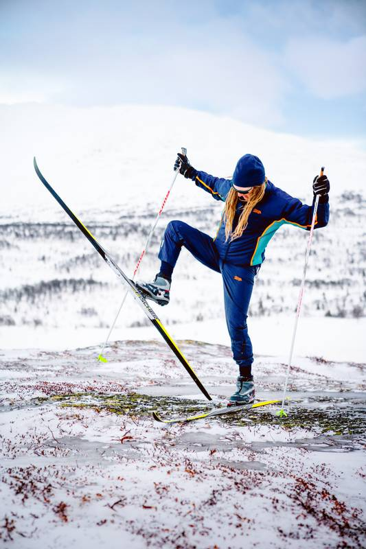 Cross-country skier in vintage clothes looking confused at his skis.