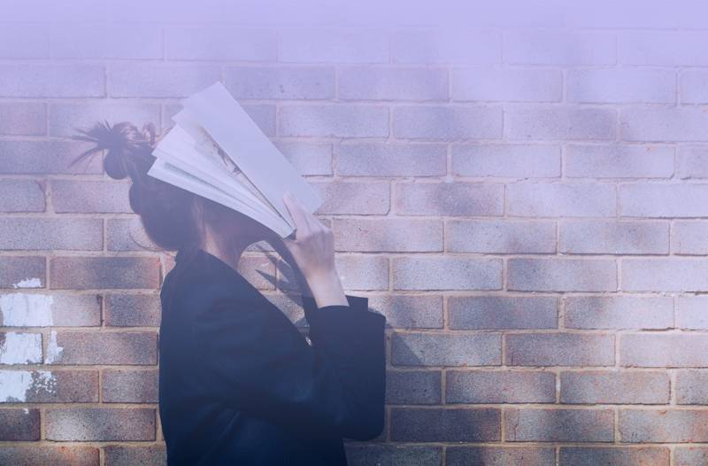 School Girl with Book in front of natural rustic red brick background holding book up to her face.